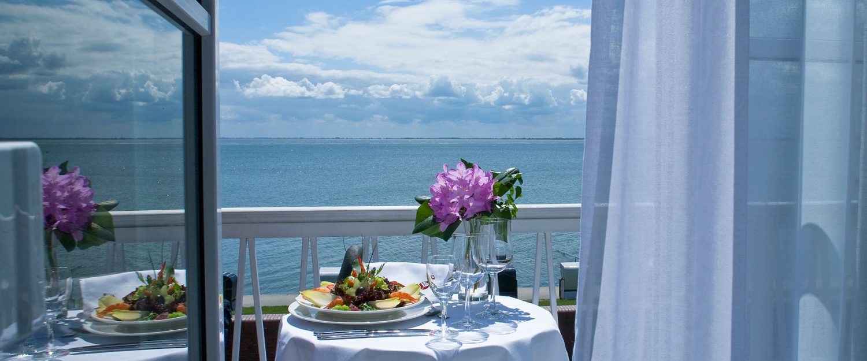 gedeckter Tisch mit Ausblick auf das Meer